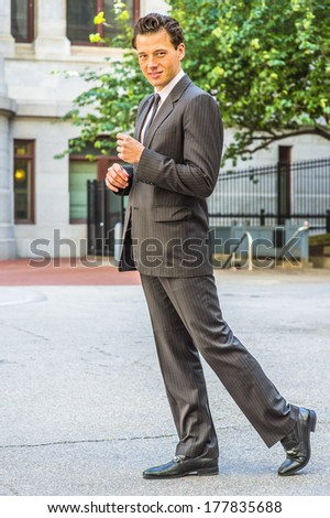 Wearing a black striped jacket, pants, tie, leather shoes,  a young businessman is walking outside an office building, turning around, looking at you. / Walking Outside - stock photo