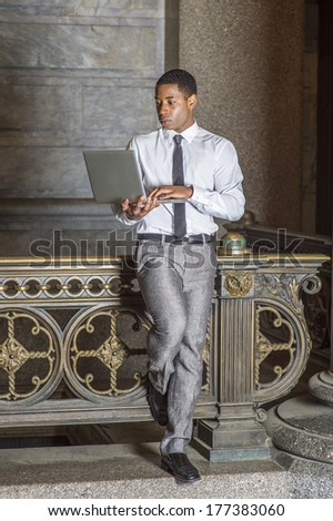 Wearing a white shirt, a black tie, gray pants, a young handsome black college student is standing by a railing in a hallway on a campus, working on a laptop computer. /Study Anywhere  - stock photo