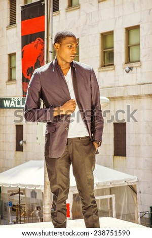 Wearing a white under wear, fashionable jacket, a hand holding a fist, a young black college student is standing on street, looking down, sad, thinking. Wall Street sign on background. - stock photo