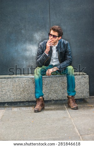 Wearing black leather jacket, blue jeans, brown boot shoes, sunglasses, a young guy with beard sitting on marble bench in corner, smoking cigarette during working break, trying mind calming down