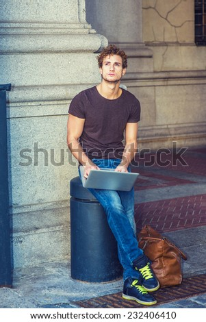 Wearing dark brown T shirt, jeans, sneakers, leather bag on the ground, a young sexy guy with curly hair is sitting on a metal stake on the street, looking up, working on laptop computer, thinking. - stock photo
