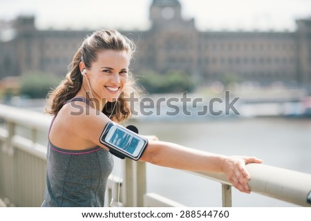Wearing her device on her arm, an athletic woman smiles over her shoulder as she leans against a guardrail above an urban river. It's summer time, the sun feels good, and the music is motivating. - stock photo