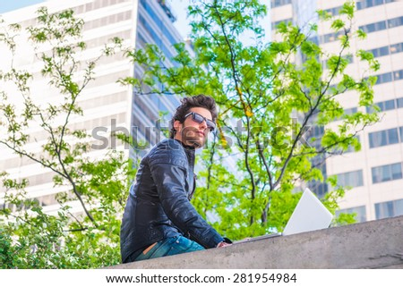 Wearing leather jacket, sunglasses, a young handsome guy with beard, working on laptop computer on the top of wall on business district in spring day, looking up, thinking. Technology in daily life.