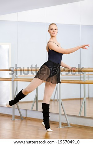 Wearing leotard and warmers athlete dances near barre and mirrors in dancing hall