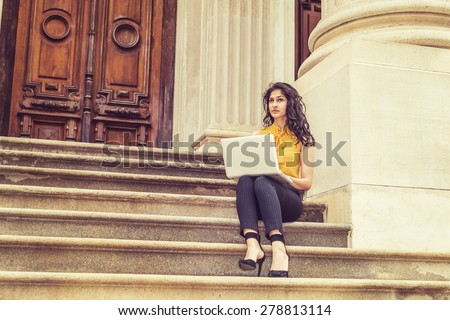 Wearing sleeveless orange shirt, striped pants, high heels, a young East Indian American college student sitting on stairs outside office building on campus, working on laptop computer, thinking. - stock photo
