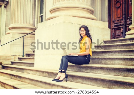 Wearing sleeveless orange shirt, striped pants, high heels, a young East Indian American college student sitting on stairs outside office building on campus, smiling, working on laptop computer. - stock photo