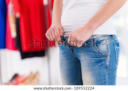 Wearing tight jeans. Cropped image of young blond woman lying on the bed and pulling on tight jeans - stock photo