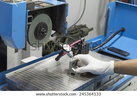 wearing white glove use indicator gauge measurement manual on Grinding machine isolate