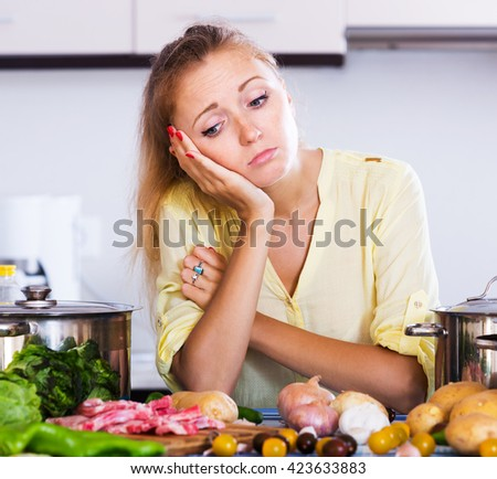 Weary housewife with meat and vegetables at kitchen table