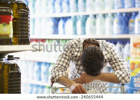 Weary Man Laying His Head on Shopping Cart - stock photo