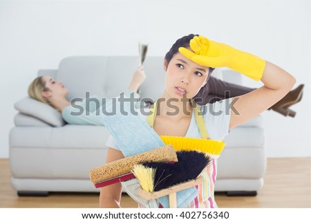 Weary woman holding cleaning tools against attractive blonde woman reading newspaper lying on couch - stock photo
