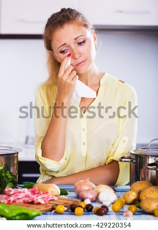 Weary woman with meat and vegetables at kitchen table