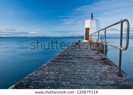 Weather beaten concrete pier, Nairn harbour, Scotland - stock photo