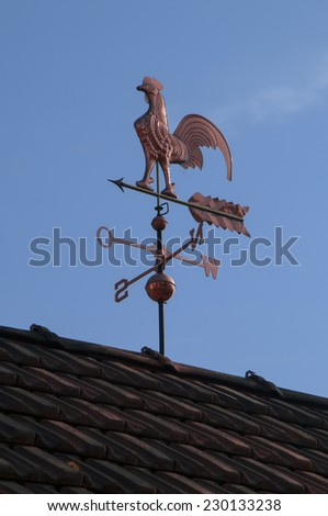 Weathercock made of copper on a roof in front of blue sky - stock photo