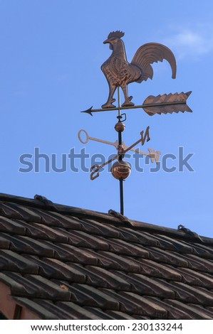 Weathercock made of copper on a roof in front of blue sky