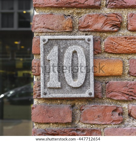 Weathered aluminum house number ten on a red brick wall - stock photo