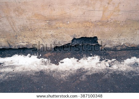 Weathered background, empty grunge urban street with line of snow and obsolete wall.  - stock photo