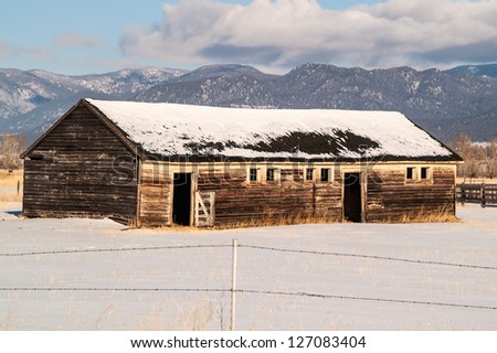 Weathered barn on a ranch in Montana in the winter with a beautiful mountain view - stock photo