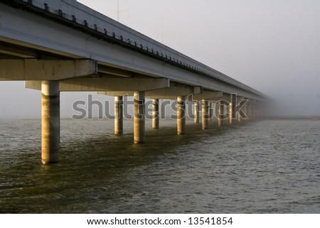 Weathered bridge disappearing into fog - stock photo