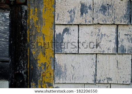 Weathered clapboard and yellow painted door frame - stock photo