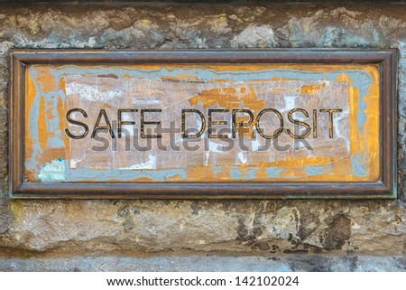 Weathered copper bank placard with the text safe deposit on an ancient brick wall - stock photo