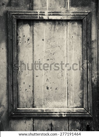 Weathered door with border frame. Aged photo. Black and white. - stock photo
