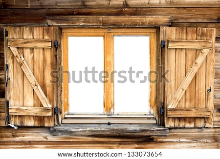 Weathered facade of a mountain hut with isolated windows - stock photo