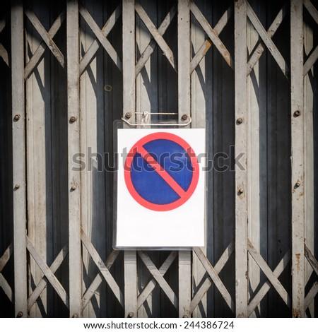 weathered garage door with no parking sign - stock photo