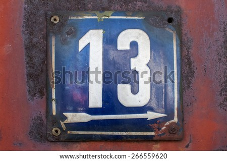 Weathered grunge square metal enameled plate of number of street address with number 13 closeup - stock photo