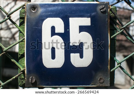 Weathered grunge square metal enameled plate of number of street address with number 65 closeup