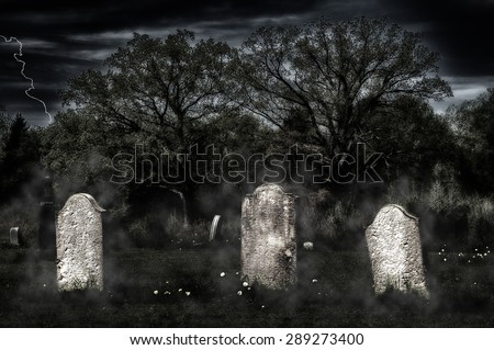 Weathered headstones in an old cemetery glow in an eerie light in the gloom, with a grainy sky and fog wisps - stock photo