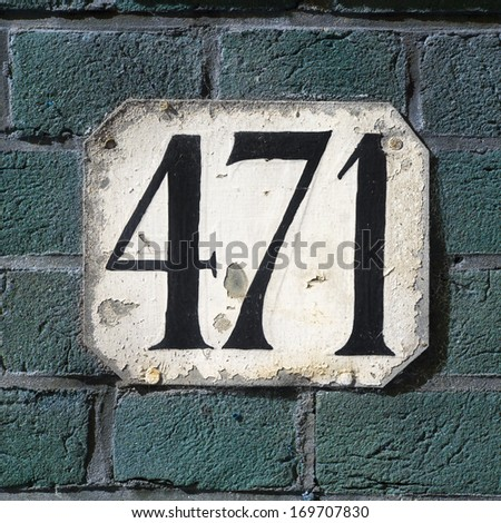 Weathered house number four hundred and seventy one on a green brick wall - stock photo