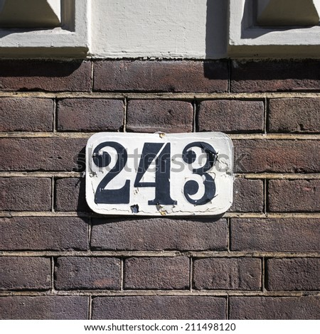 weathered house number two hundred and forty three - stock photo
