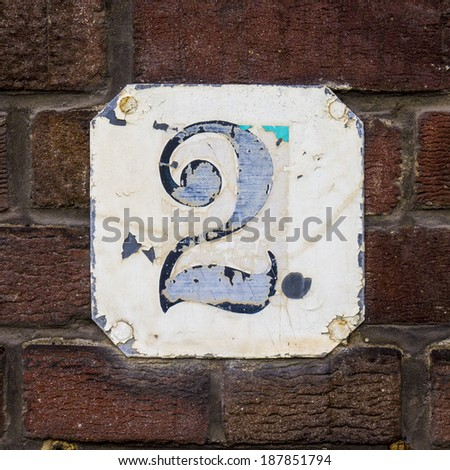 weathered house number two on a metal plate - stock photo