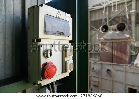 Weathered industrial electricity cabin, electrical junction box  with red shut off (stop) button for emergencies. Industrial setting in the background.