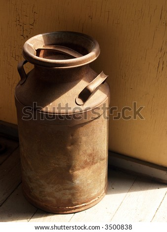 Weathered Old Milk Can in Doorway