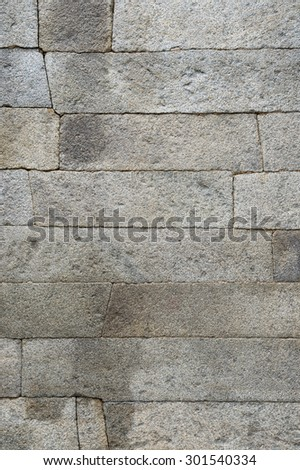 Weathered old textured stone wall background in gray tones - stock photo