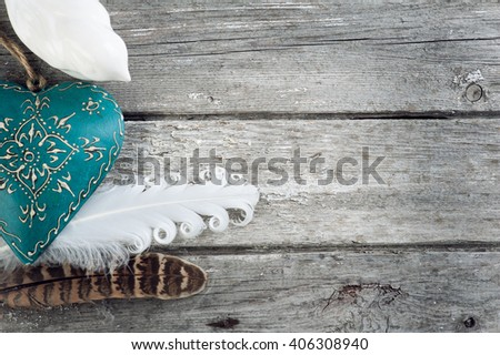 Weathered old wooden background with feathers and blue heart. Copy Space  - stock photo
