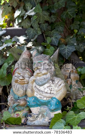 weathered retro garden decoration with garden gnomes - stock photo
