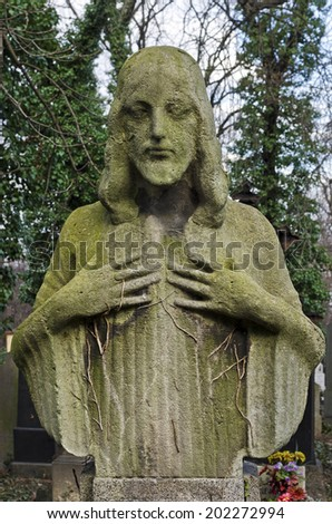 Weathered statue of Jesus - tombstone at old Prague cemetery, Czech republic, Europe - stock photo