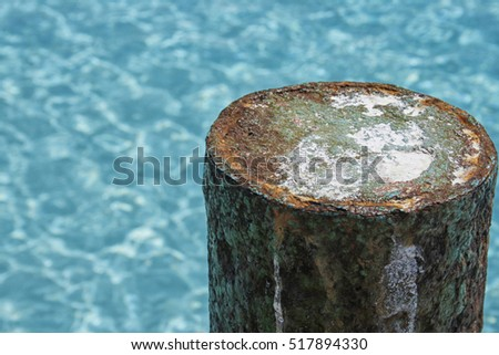 weathered steel docking part on a jetty against background of bright blue caribbean sea