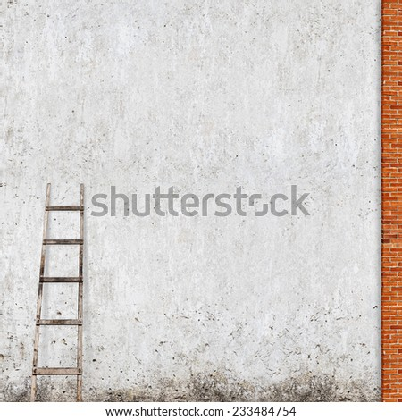 weathered stucco wall, red brick frame with a wooden ladder background - stock photo