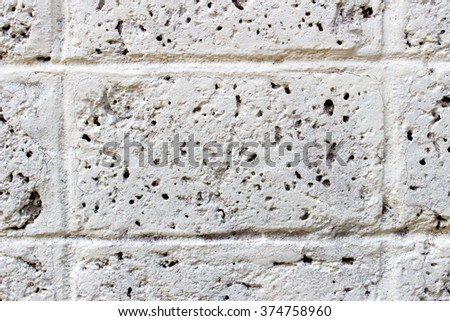 Weathered texture of stained old dark white and gray brick wall background, grungy rusty blocks of light stone-work technology, colorful horizontal architectur - stock photo