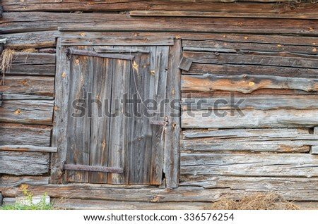 weathered wooden cottage wall made of debarked spruce trunks with closed window shutter