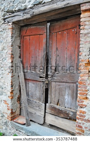 weathered wooden door in an old wall - stock photo