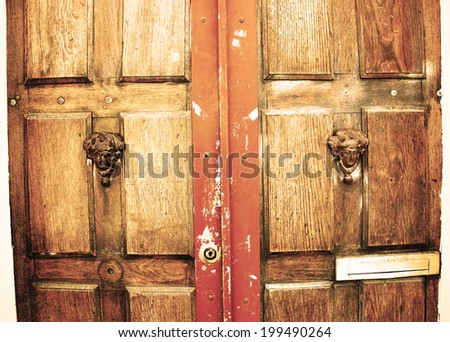 Weathered wooden door with decorative handles - in shape of human head with wreath on it (like Roman patrician) - and a slot for the letters. Paris, France. Aged photo. - stock photo