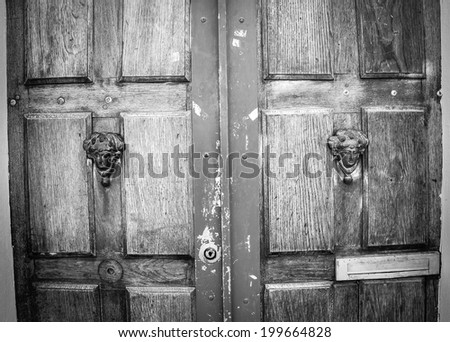 Weathered wooden door with decorative handles - in shape of human head with wreath on it (like Roman patrician). Paris, France. Aged photo. Black and white.