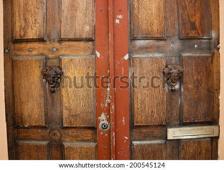 Weathered wooden door with decorative handles - in shape of human head with wreath on it (like Roman patrician). Paris, France.  - stock photo