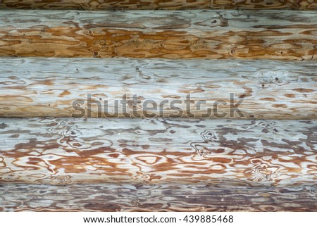 Weathered wooden logs wall of rural house background - stock photo