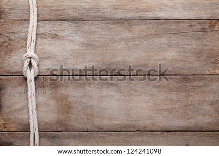 Weathered wooden table background with rope reef knot, top view - stock photo